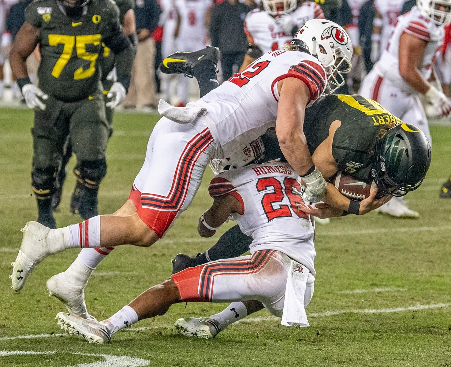 Utah's defensive tackle Mika Tafua, #42, and safety Terrell Burgess, #26, takes down Oregon's quarterback Justin Herbert, #10, after he tucks the ball in and run it for himself.  The University of Oregon Ducks defeated the University of Utah Utes 37-15 for the Pac 12 Championship Friday night at Levi's Stadium. Oregon's running back CJ Verdell, #7, rushed for 203 all-purpose yard along with three touchdowns for the night. Verdell was named the games M-V-P for his performace. Oregon's safey Brady Breeze, #25, contributed 9 tackles and one interception. Oregon's defensive end Kayvon Thibodeaux, #5, sacked Utah's quarterback Tyler Huntly, #1, for a total of three times. Oregon's quarterback Justin Herbert, #10, passed for 193 yards with one touchdown. The Oregon Ducks will represent the Pac 12 for the upcoming Rose Bowl game in the new year. Photo by Jeffrey Price