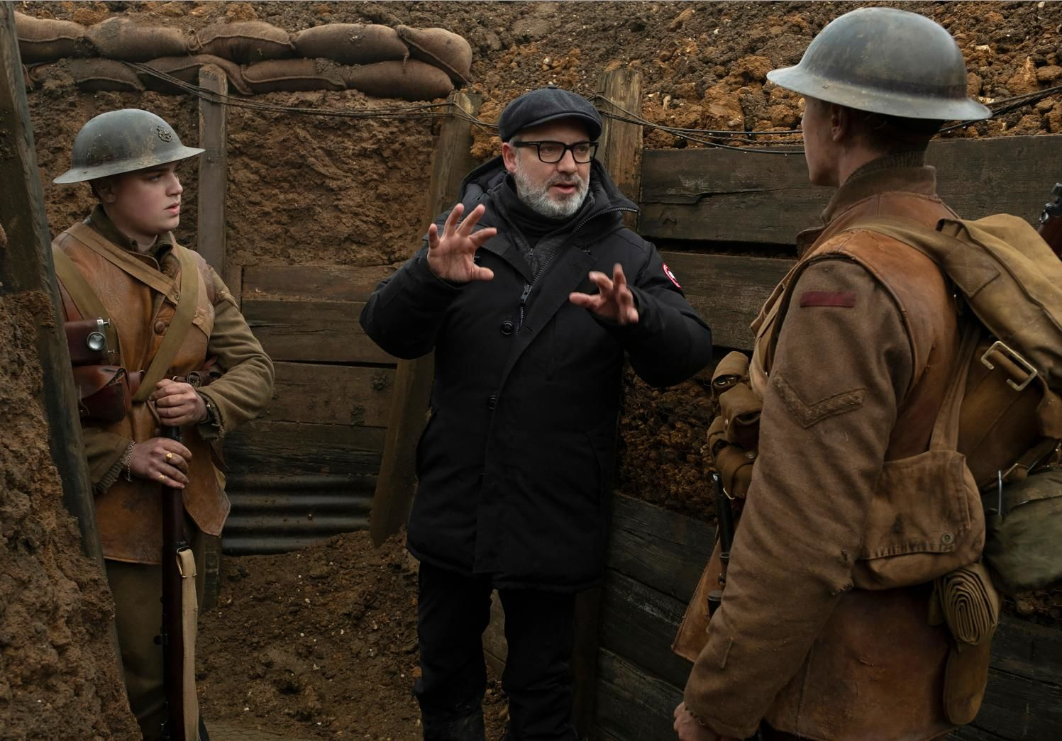 "This image released by Universal Pictures shows Dean-Charles Chapman, left, director Sam Mendes, center, and George MacKay on the set of ""1917."" On Monday, Jan. 13, Mendes was nominated for an Oscar for best director for his work on the film. (François Duhamel/Universal Pictures via AP)"