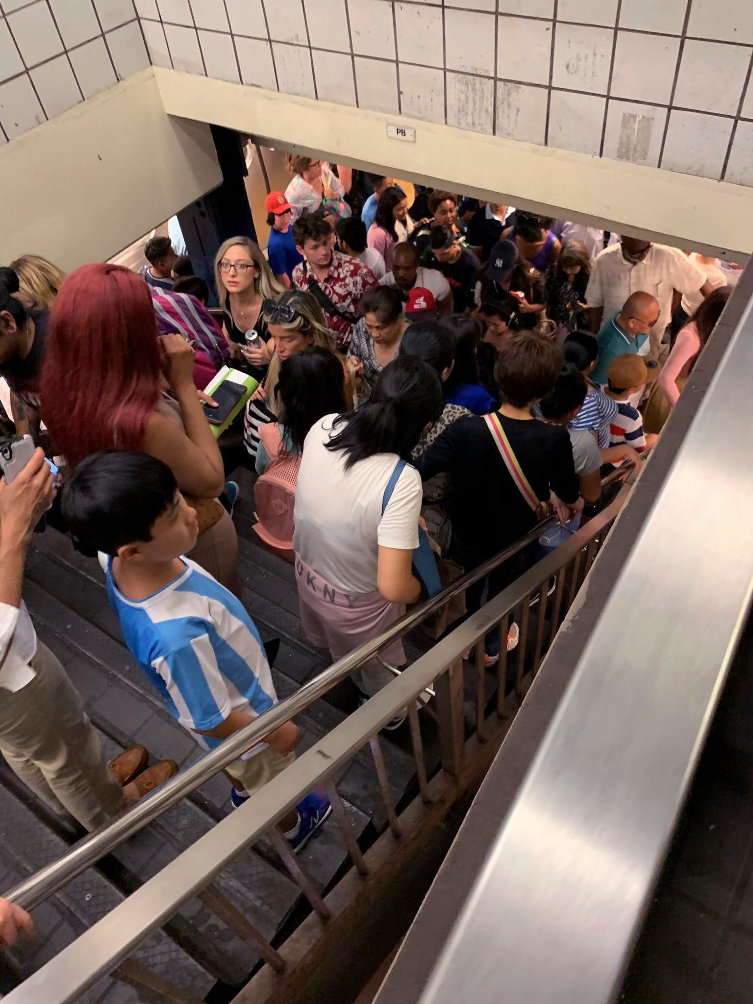 Commuters fill the stairs and line the platform at a New York City subway station as train service on seven lines came to a halt, Friday, July 19, 2019 in New York. (Kenneth Ferrone via AP)