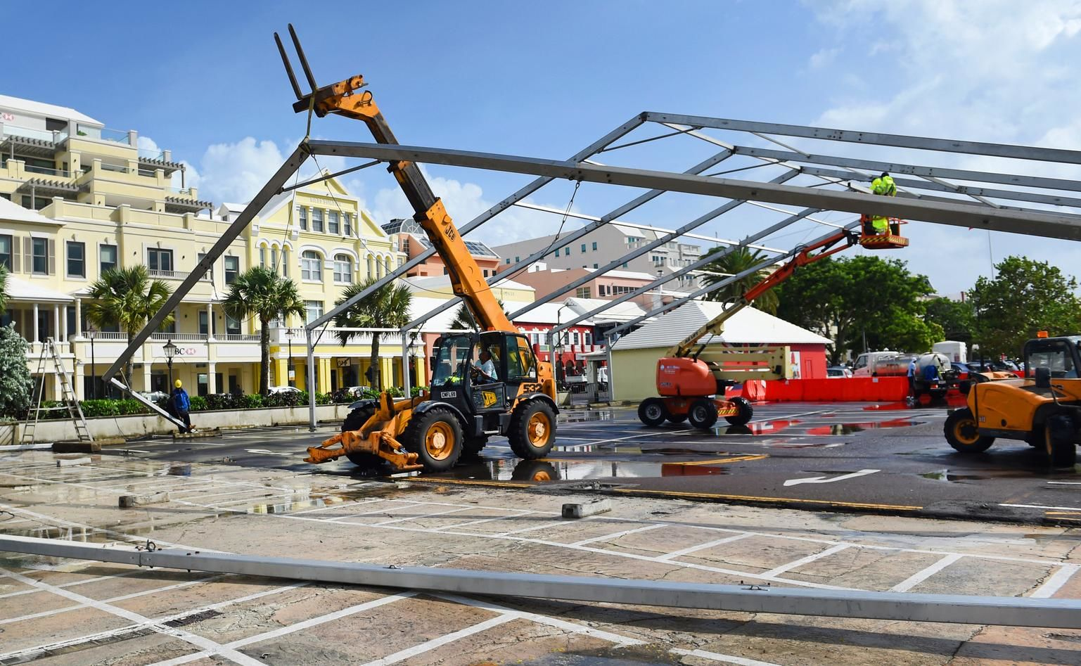 Workers take down a tent frame in preparation for Hurricane Humberto in Hamilton, Bermuda, Wednesday, Sept. 18, 2019. Bermuda's government called up troops and urged people on the British Atlantic island to make final preparations for an expected close brush Wednesday with Hurricane Humberto, a powerful Category 3 storm. Authorities ordered early closings of schools, transportation and government offices. (AP Photo/Akil J. Simmons)