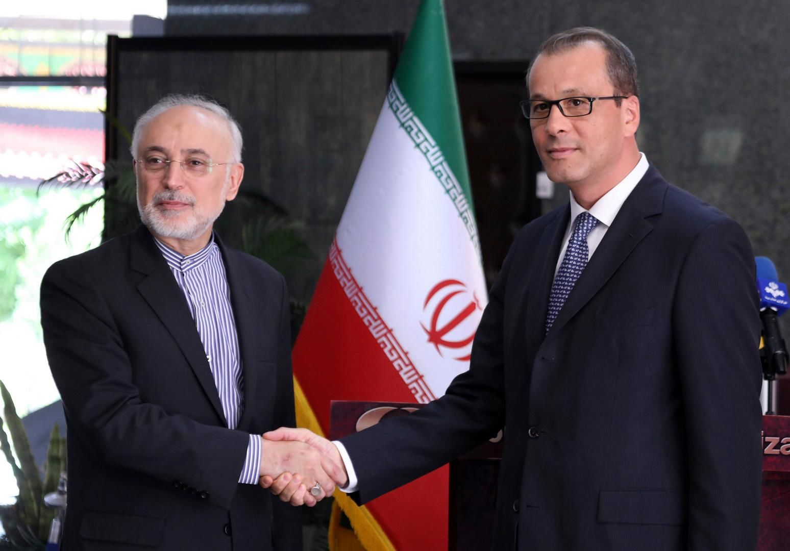 In this photo released by the Atomic Energy Organization of Iran, the head of the organization Ali Akbar Salehi, left, shakes hands with Acting Director-General of the International Atomic Energy Agency, IAEA, Cornel Feruta during their meeting in Tehran, Iran, Sunday, Sept. 8, 2019. (Atomic Energy Organization of Iran via AP)
