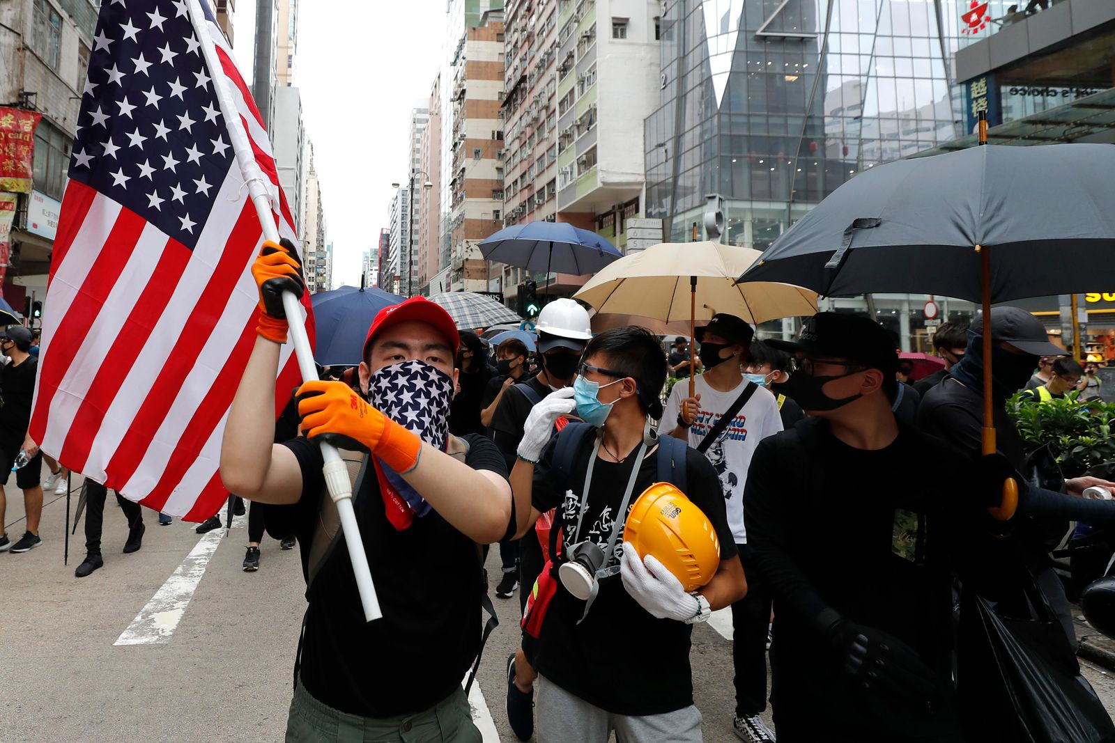 A protester carries a U.S. flag as they march through the Mong Kok neighborhood during a demonstration in Hong Kong, Saturday, Aug. 3, 2019. Hong Kong protesters ignored police warnings and streamed past the designated endpoint for a rally Saturday in the latest of a series of demonstrations targeting the government of the semi-autonomous Chinese territory. (AP Photo/Vincent Thian)