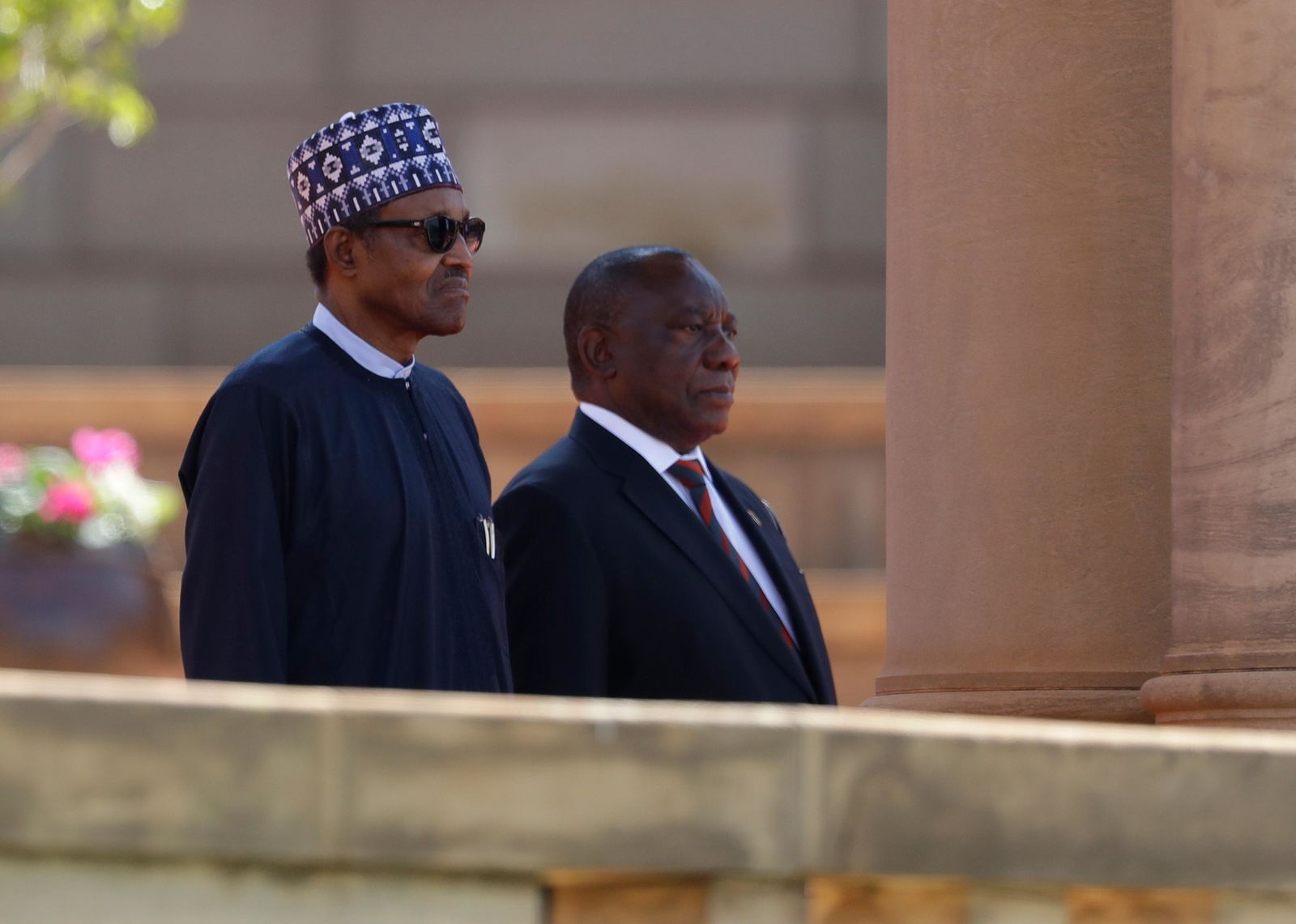 Nigerian President Muhammadu Buhari, left, stands with South Africa's leader Cyril Ramaphosa for the playing of the national anthems at a welcoming ceremony in Pretoria, South Africa Thursday, Oct. 3, 2019.{ } (AP Photo/Themba Hadebe)
