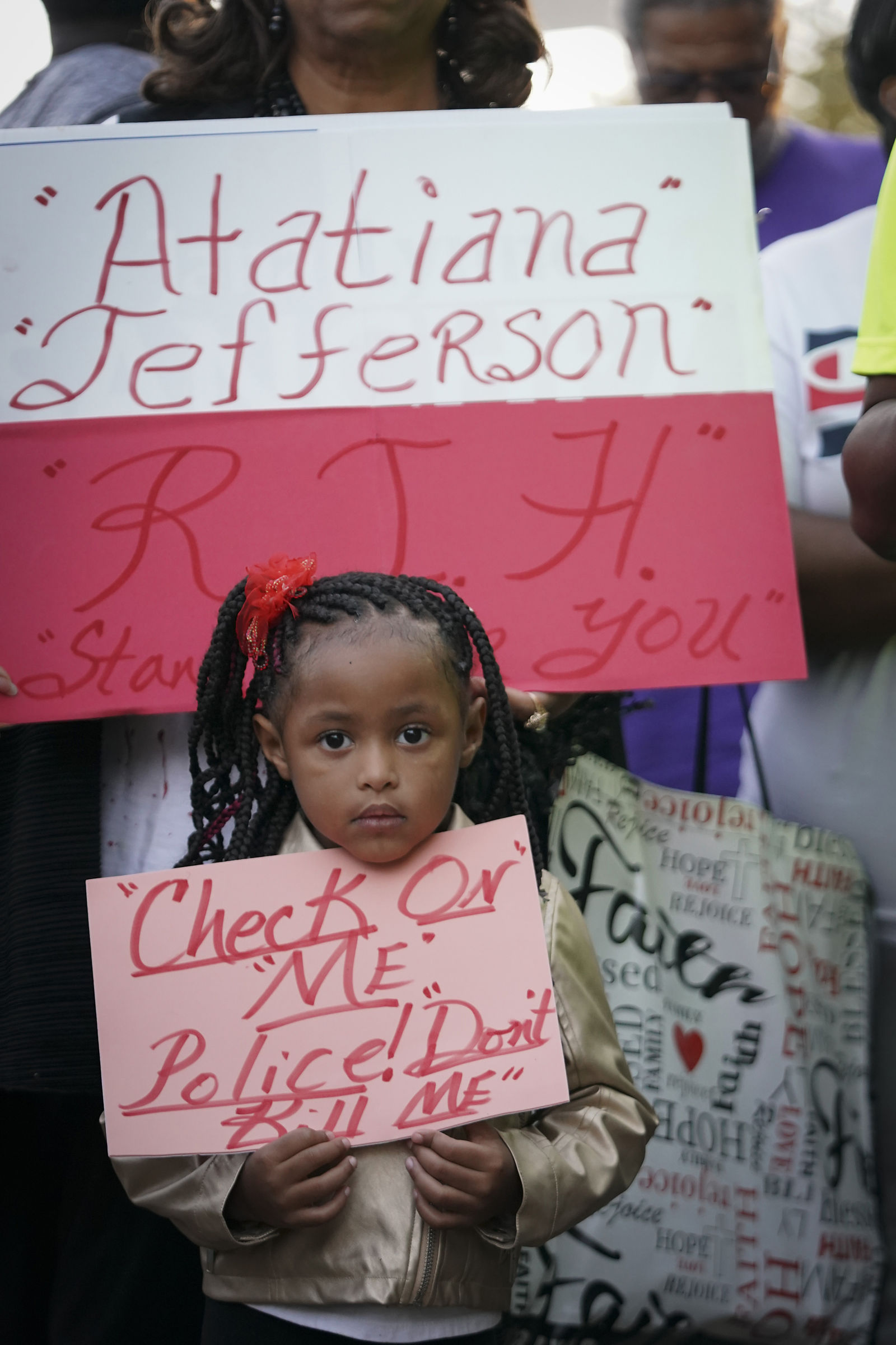 "Trinity Ford, 4, joins the crowd gathered during a community vigil for Atatiana Jefferson on Sunday, Oct. 13, 2019, in Fort Worth, Texas. A white police officer who killed the black woman inside her Texas home while responding to a neighbor's call about an open front door ""didn't have time to perceive a threat"" before he opened fire, an attorney for Jefferson's family said. (Smiley N. Pool/The Dallas Morning News via AP)"