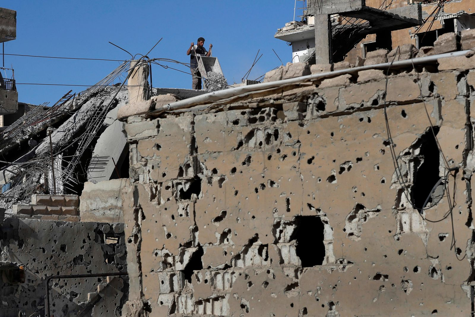 In this Thursday, April 5, 2018 photo, a man removes rubble from his house that was damaged during fighting between U.S.-backed Syrian Democratic Forces fighters and Islamic State militants, in Raqqa, Syria.  U.S. President Donald Trump's decision Wednesday Dec. 19, 2018, to withdraw U.S. troops from Syria has rattled Washington's Kurdish allies, who are its most reliable partner in Syria and among the most effective ground forces battling the Islamic State group. (AP Photo/Hussein Malla, FILE)