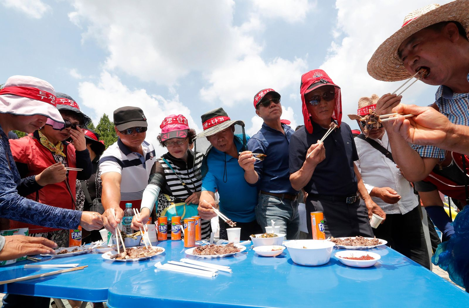 Members of the Korean Dog Meat Association eat dog meat during a rally to support eating the meat in front of the National Assembly in Seoul, South Korea, Friday, July 12, 2019. July 12 is the day South Koreans eat healthy foods such as dog meat in the belief it would help them survive heat during summer. (AP Photo/Ahn Young-joon)