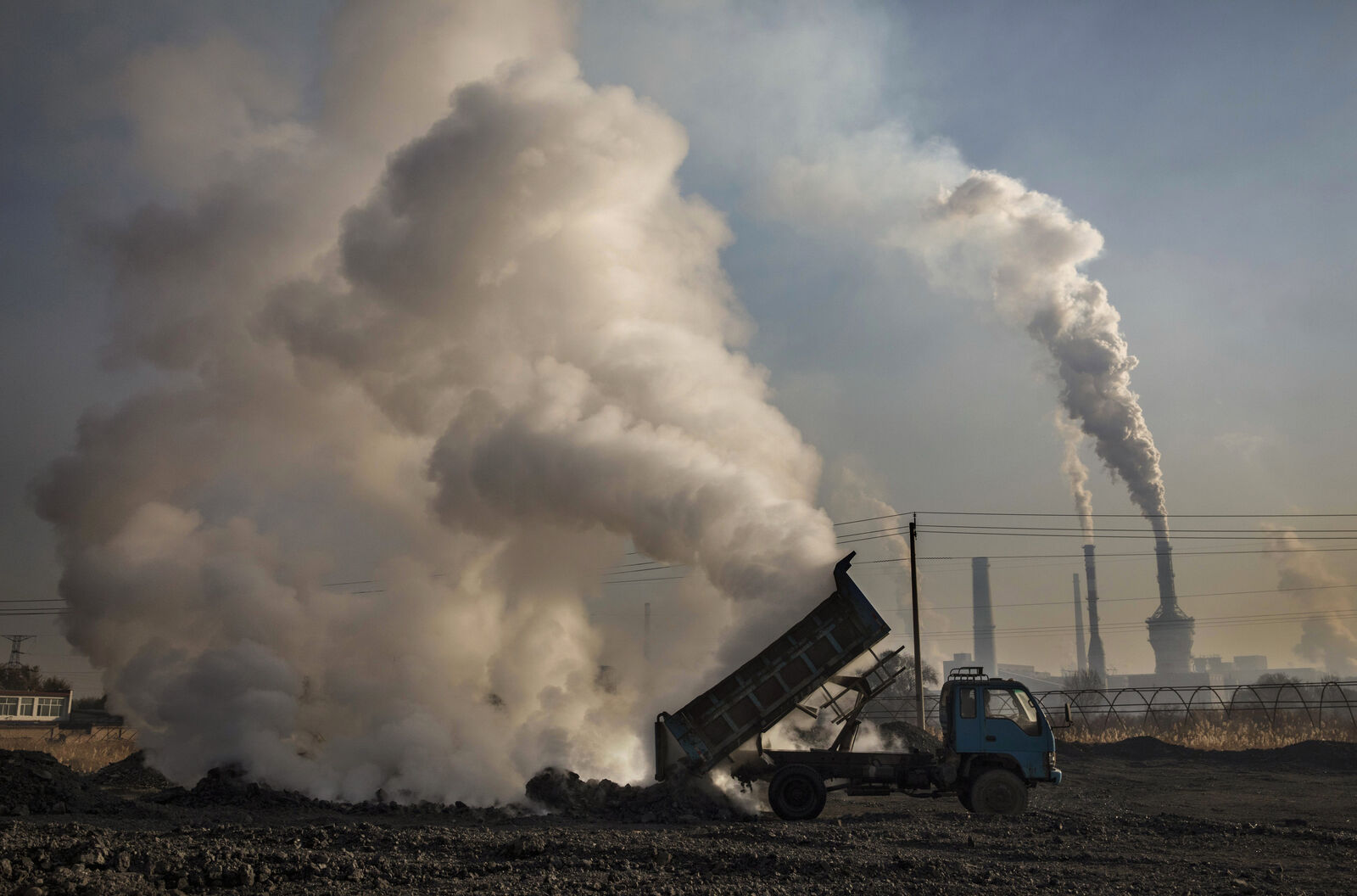FILE: A Chinese labourer unloads waste coal and stone as smoke and steam rises next to an unauthorized steel factory on November 3, 2016 in Inner Mongolia, China. (Photo by Kevin Frayer/Getty Images)