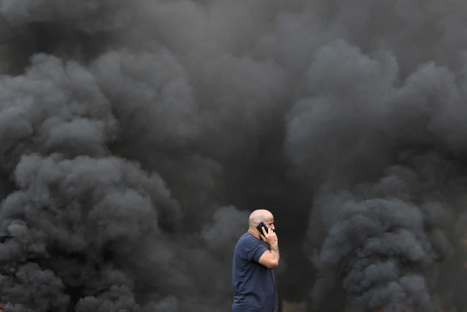 A man speaks on his smartphone while walking by black smoke from burning tires that were set on fire to block a road during a protest against government's plans to impose new taxes in Beirut, Lebanon, Friday, Oct. 18, 2019.{ } (AP Photo/Hassan Ammar)