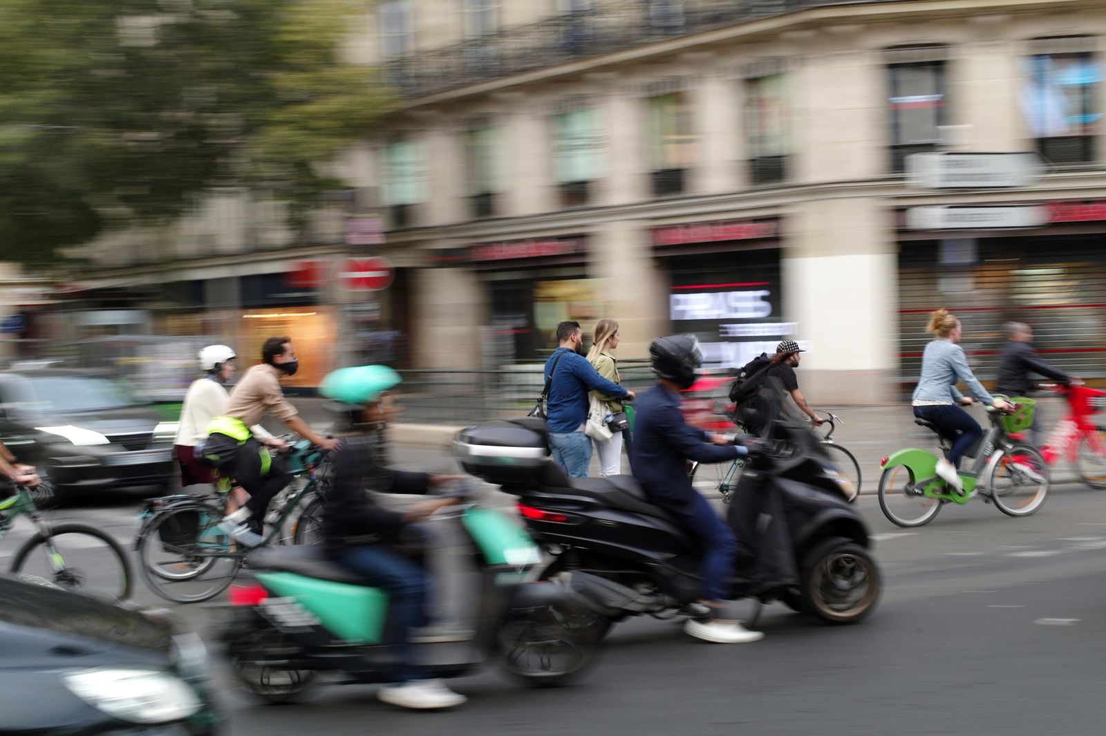 People ride bicycles and scooters in a street of Paris, Friday, Sept. 13, 2019. Paris metro warns over major strike, transport chaos Friday. (AP Photo/Thibault Camus)