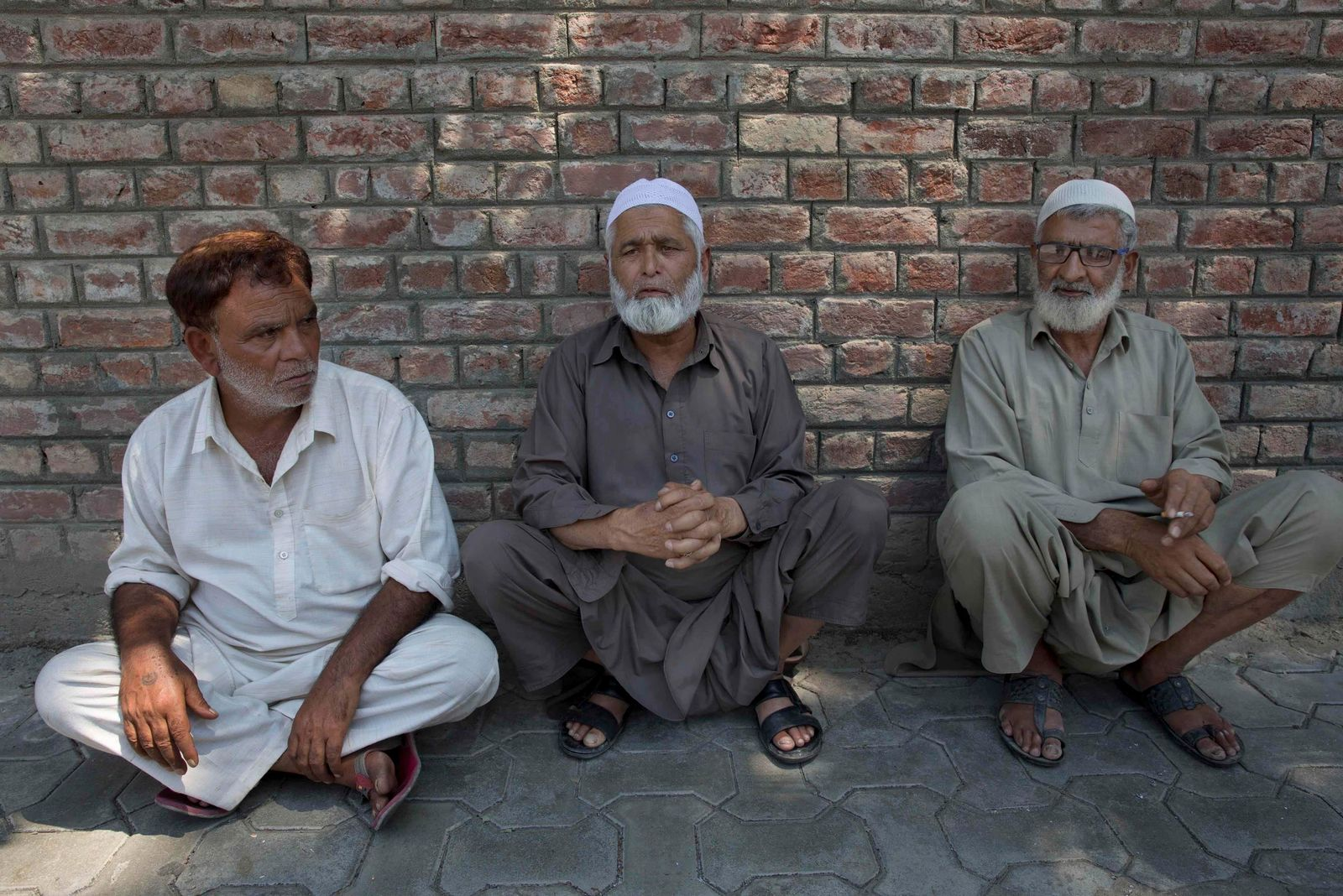 Kashmiri men sit on a footpath outside a police station waiting to hear about their relatives who were detained during night raids in Srinagar, Indian controlled Kashmir, Tuesday, Aug. 20, 2019. Authorities say thousands of people, mostly young male protesters, have been arrested and detained in Indian-administered Kashmir amid an ongoing communications blackout and security lockdown. (AP Photo/ Dar Yasin)