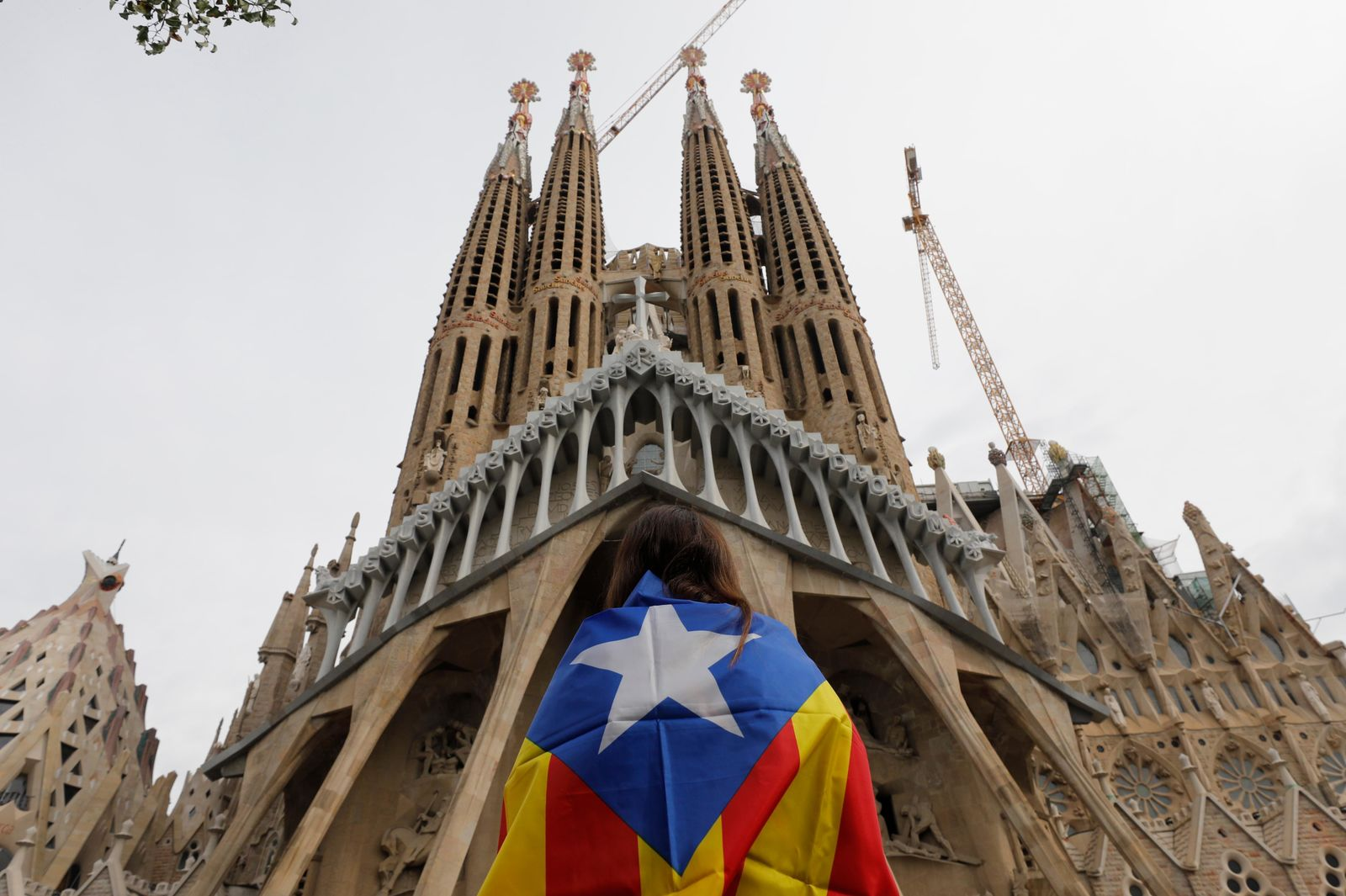 "A protester draped with an ""estelada"" or independence flag stands outside outside the Sagrada Família basilica during pro-independence gathering on the fifth day of protests over the conviction of a dozen Catalan independence leaders in Barcelona, Spain, Friday, Oct. 18, 2019. (AP Photo/Bernat Armangue)"