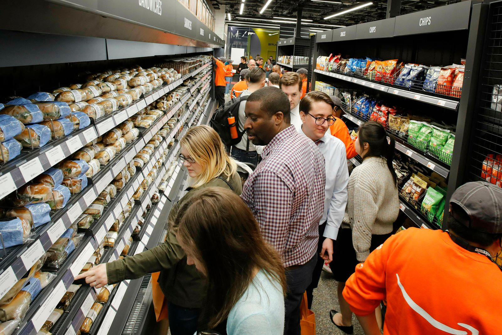 FILE - In this May 7, 2019, file photo customers shop in a newly-opened Amazon Go store in New York. . (AP Photo/Mark Lennihan, File)