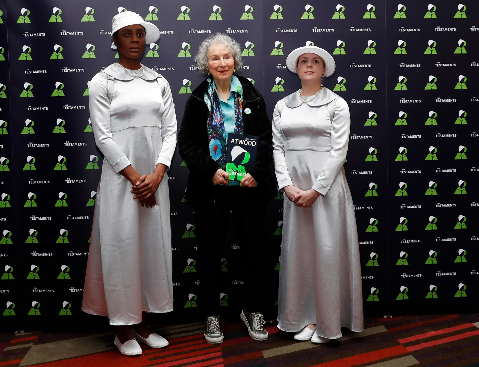 Canadian author Margaret Atwood poses with two models for a photograph during a press conference at the British Library to launch her new book 'The Testaments' in London, Tuesday, Sept. 10, 2019. (AP Photo/Alastair Grant)