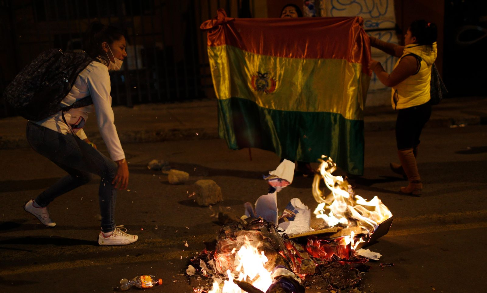 Supporters of opposition presidential candidate Carlos Mesa burn campaign posters of ruling party congressional candidates outside the Supreme Electoral Court where election ballots are being counted in La Paz, Bolivia, Monday, Oct. 21, 2019.{ } (AP Photo/Juan Karita)