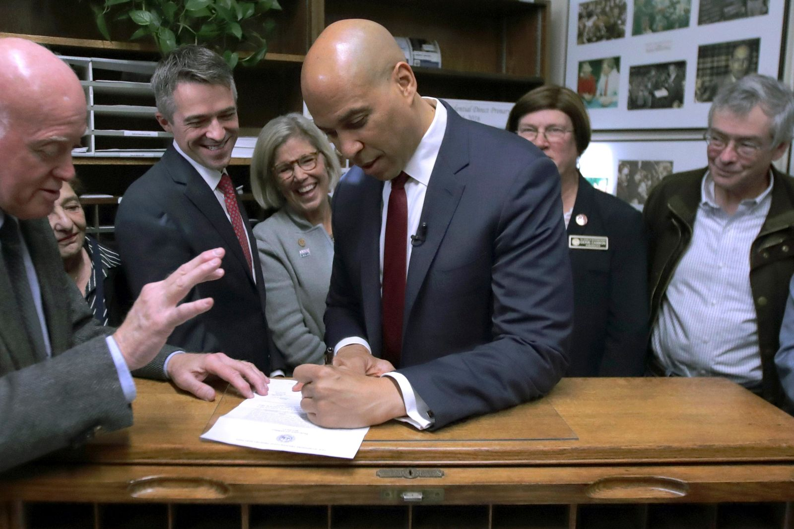 Democratic presidential candidate Sen. Cory Booker, D-N.J., files to have his name listed on the New Hampshire primary ballot, Friday, Nov. 15, 2019, in Concord, N.H. At left is New Hampshire Secretary of State Bill Gardner. (AP Photo/Charles Krupa)