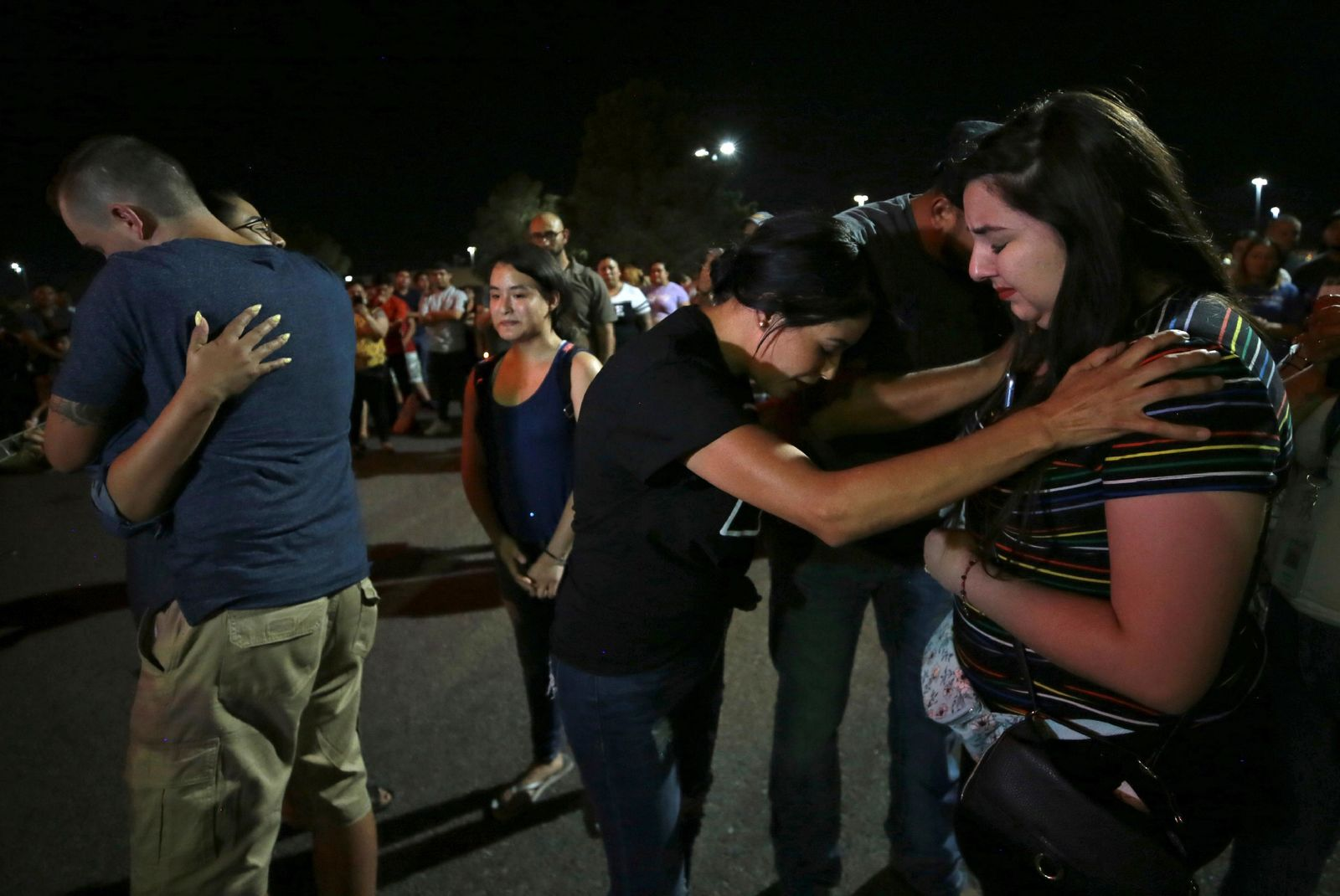 Members of Iglesia Cristiana Manatial en el Desierto pray with El Pasoans who came to hold vigil Monday, Aug. 5, 2019, outside the Walmart in El Paso, Texas, where a mass shooting took place on Saturday. (Mark Lambie/The El Paso Times via AP)