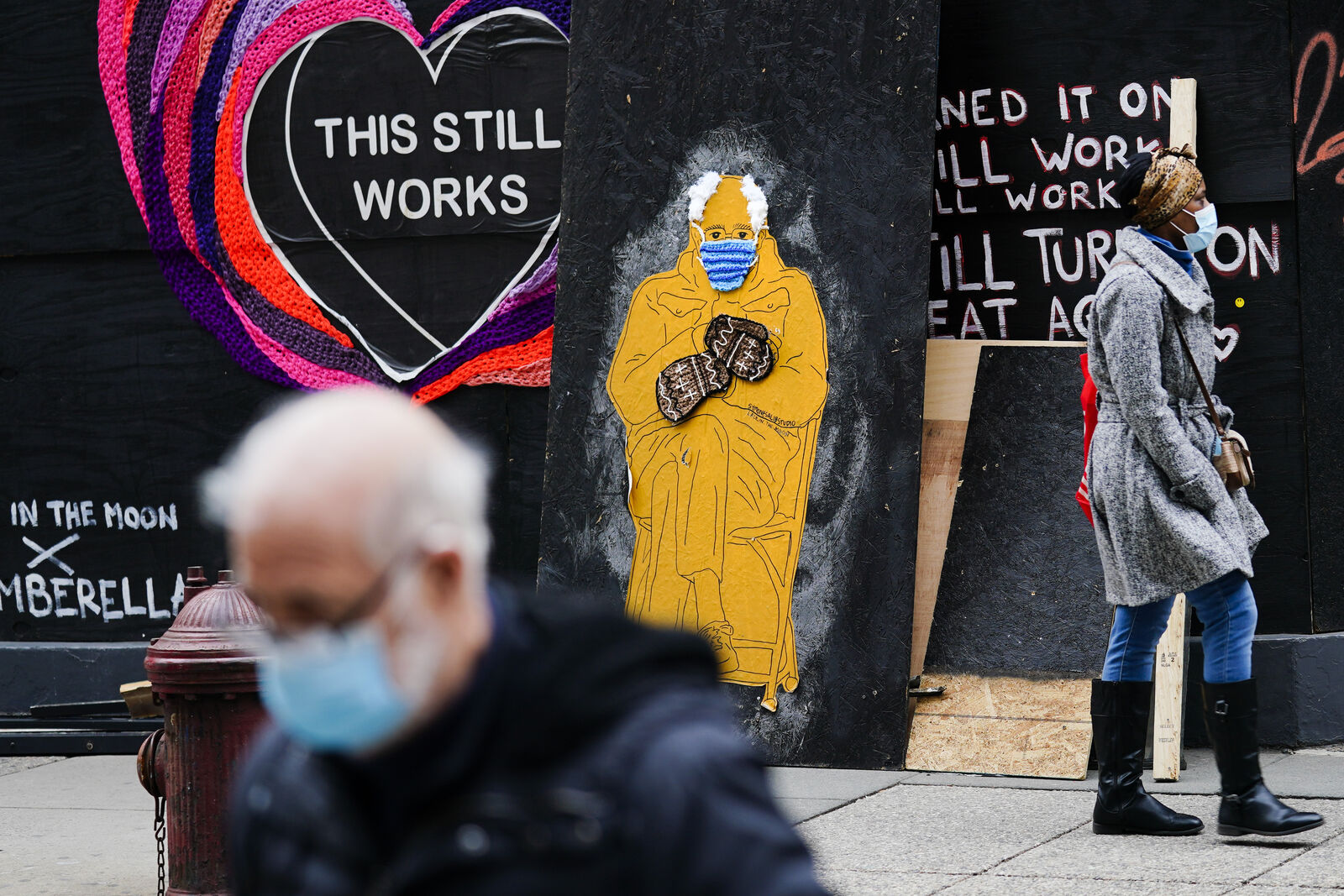 People wearing face masks as a precaution against the coronavirus walk past a depiction of Sen. Bernie Sanders, I-Vt., in Philadelphia, Monday, Jan. 25, 2021. (AP Photo/Matt Rourke)