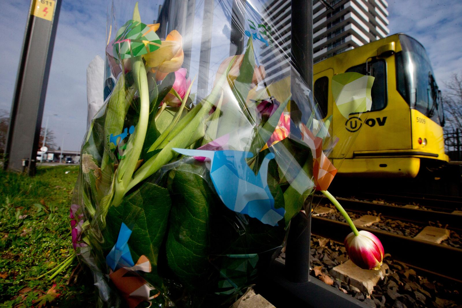 A tram passes flowers placed at the site of a shooting incident on a tram, in Utrecht, Netherlands, Tuesday, March 19, 2019. (AP Photo/Peter Dejong)