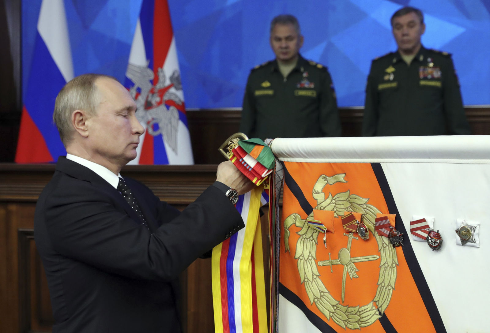 Russian President Vladimir Putin, left, pins a medal on a military banner during a meeting with the top military staff in the Russian Defense Ministry's headquarters in Moscow, Russia, Tuesday, Dec. 18, 2018. Putin said that new Russian weapons have no foreign equivalents, helping ensure the nation's security for decades to come. (Mikhail Klimentyev, Sputnik, Kremlin Pool Photo via AP)