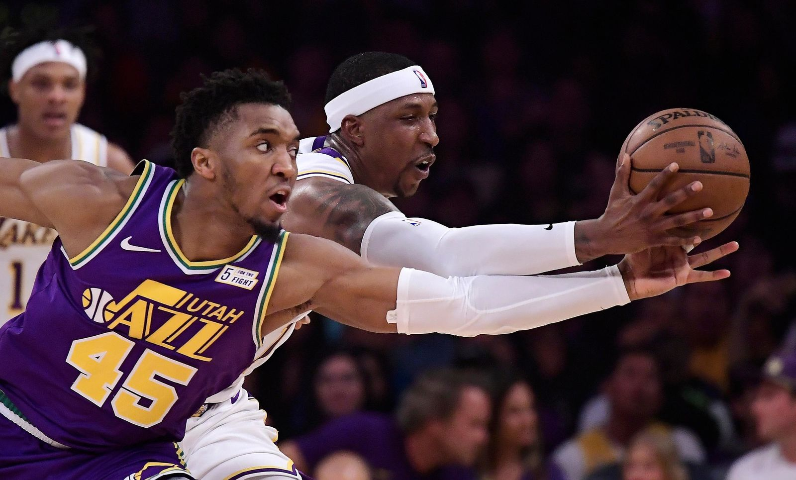 Utah Jazz guard Donovan Mitchell, left, and Los Angeles Lakers guard Kentavious Caldwell-Pope go after a loose ball during the first half of an NBA basketball game Sunday, April 7, 2019, in Los Angeles. (AP Photo/Mark J. Terrill)