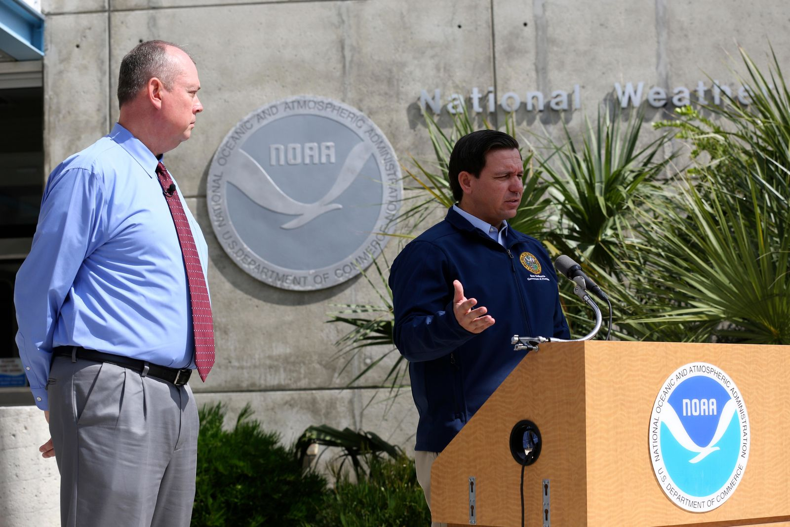 National Hurricane Center Director Ken Graham, left, looks on as Florida Gov. Ron DeSantis speaks about Tropical Storm Dorian outside of the the National Hurricane Center, Thursday, Aug. 29, 2019, in Miami. (AP Photo/Lynne Sladky)