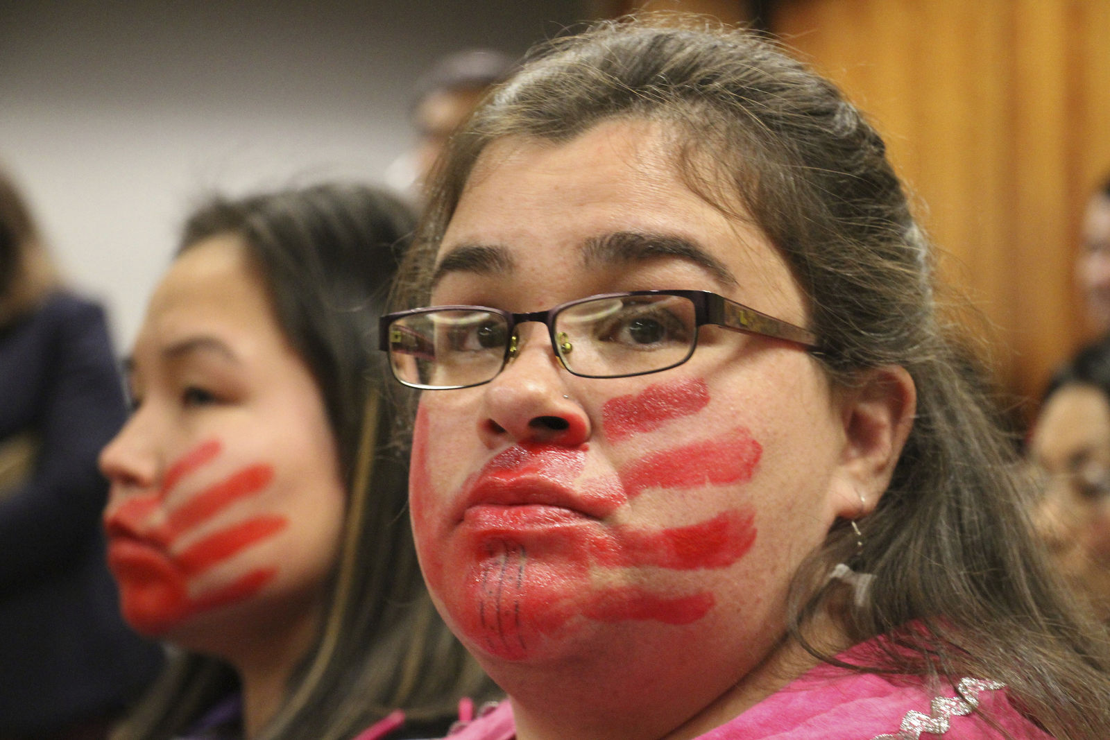 Joanne Sakar, left, and Natasha Gamache hold a silent protest in a courtroom, to highlight what Gamache says is Alaska's history of not properly investigating, prosecuting or sentencing perpetrators of crimes against Alaska Native women, in Anchorage, Alaska, Monday, Oct. 21, 2019. They attended the arraignment for Brian Steven Smith, who faces 14 charges in the deaths of two Alaska Native women. The red hands painted on their faces represents the silencing of indigenous women. (AP Photo/Mark Thiessen)