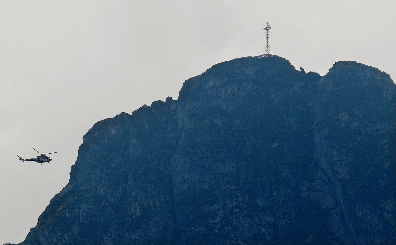 Rescuers in a helicopter checking the slopes of the Giewont peak for missing persons and anyone who might need help in the Tatra Mountains in Poland, Friday, Aug. 23, 2019. (AP Photo/Bartlomiej Jurecki)