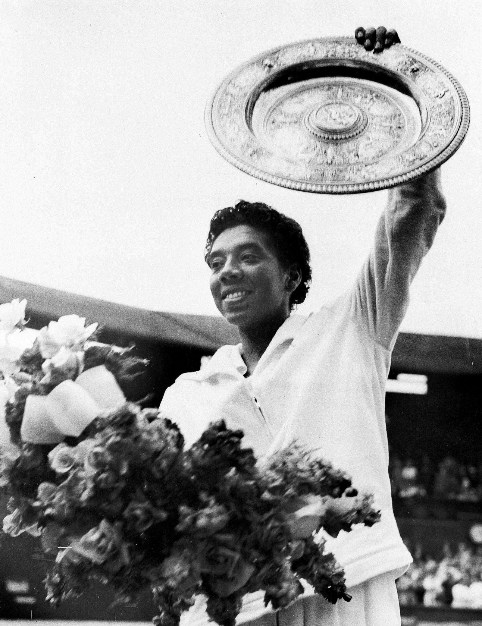 FILE - In this July 5, 1958, file photo, New York's Althea Gibson waves the winner's plate aloft after she defeated Britain's Angela Mortimer in the women's singles tennis final at Wimbledon, England. Gibson won an amazing 11 Grand Slam titles in three years from 1956-58, including the French Open, Wimbledon and U.S. Open. On Monday, Aug. 26, 2019, the USTA will unveil a statue in her honor at the U.S. Open. (AP Photo/File)