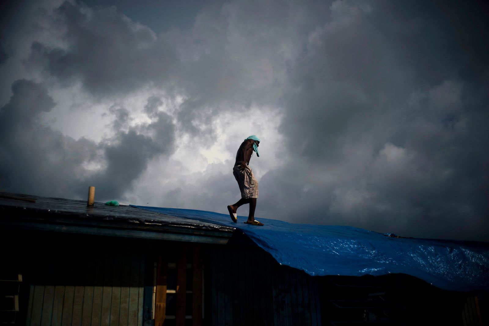 "Trevon Laing walks the roof of his house to repair the damage made by Hurricane Dorian, in Gold Rock Creek, Grand Bahama, Bahamas, Thursday Sept. 12, 2019. Trevor says ""After the hurricane they had me for dead, My momma was crying."" When he returned, he said he found his brother crying on the front porch.""I'm like, 'Hey, I'm not dead! You guys have no faith in me. I'm a survivor,'"" he said, adding with a laugh, ""He was shocked and mad at the same time."" (AP Photo / Ramon Espinosa)"