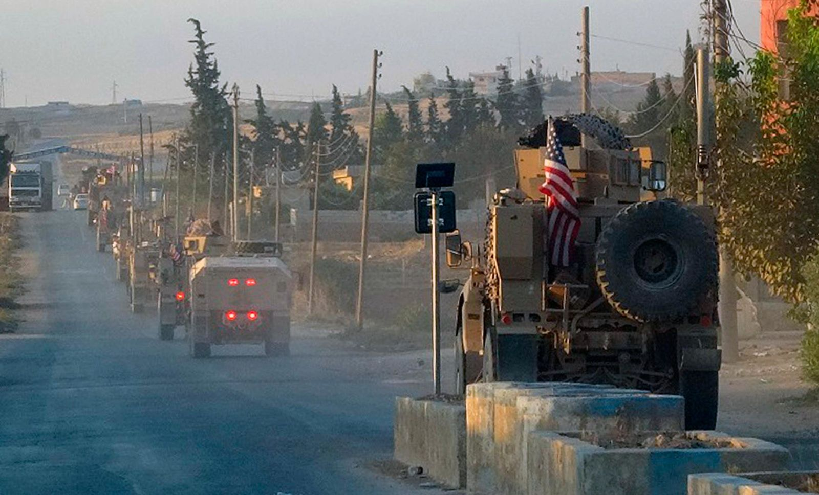 In this image provided by Hawar News Agency, ANHA, U.S. military vehicles travel down a main road in northeast Syria, Monday, Oct. 7, 2019. U.S.-backed Kurdish-led forces in Syria said American troops began withdrawing Monday from their positions along Turkey's border in northeastern Syria. (ANHA via AP)