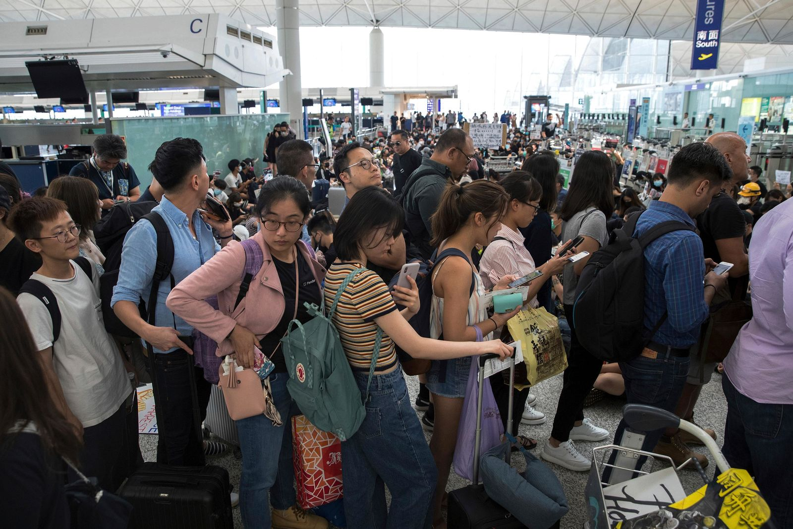 Travelers line up as protesters hold a sit-in rally at the departure gate of the Hong Kong International Airport in Hong Kong, Tuesday, Aug. 13, 2019. . (AP Photo/Vincent Thian)