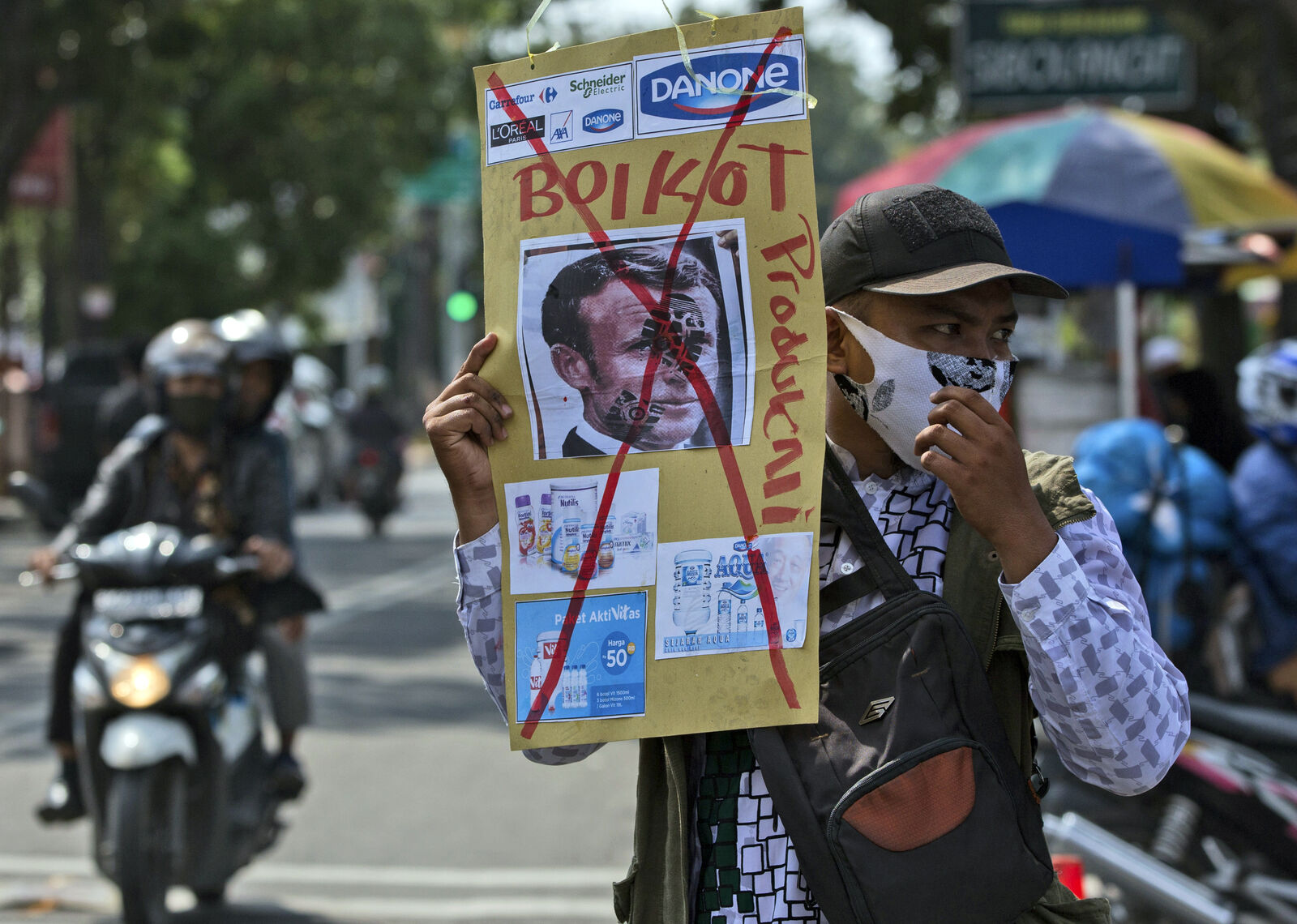 A Muslim man holds a defaced poster of French President Emmanuel Macron during a protest at Al Jihad mosque in Medan, North Sumatra, Indonesia, Friday, Oct. 30, 2020.{ } (AP Photo/Binsar Bakkara)