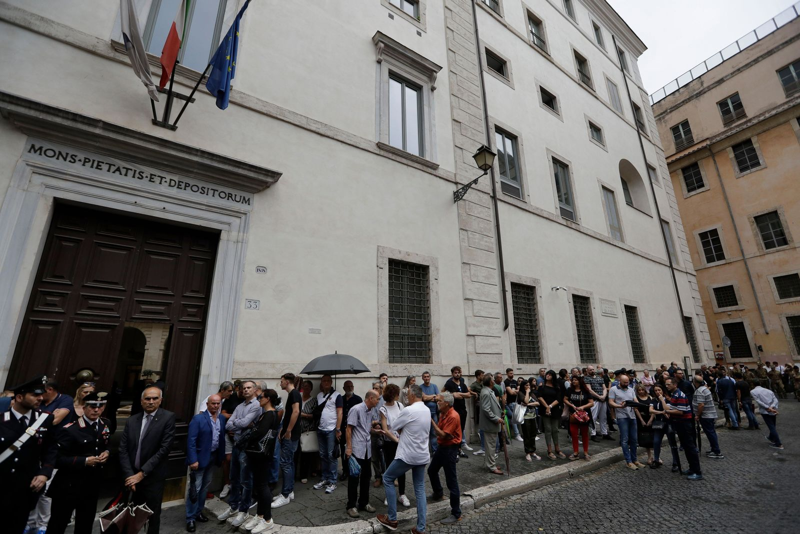 People line up to pay respect in the church where Carabinieri officer Mario Cerciello Rega was laid in state, in Rome, Sunday, July 28, 2019. In a statement Saturday, Carabinieri officers investigating the death of Cerciello Rega, 35, said two young American tourists have been detained for alleged murder and attempted extortion. (AP Photo/Andrew Medichini)