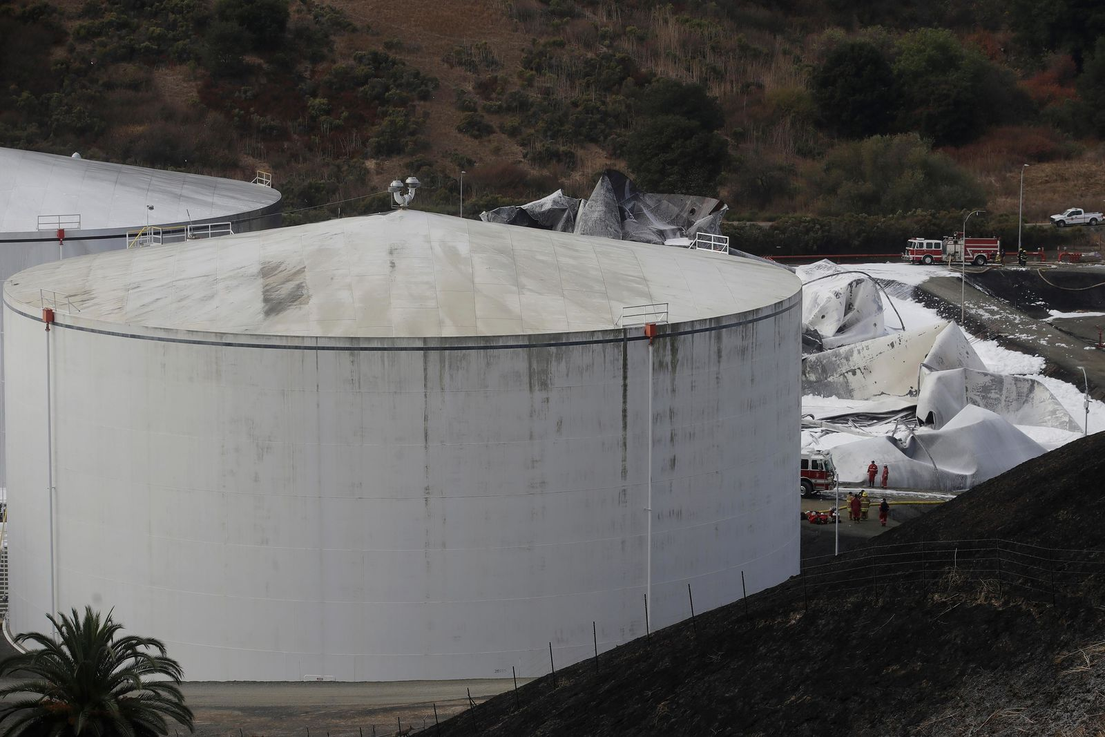 Fire and emergency crews walk past damage from a Tuesday fire at NuStar Energy fuel storage facility in Crockett, Calif., Wednesday, Oct. 16, 2019. Officials were trying to determine Wednesday if a 4.5 magnitude earthquake triggered an explosion at a fuel storage facility in the San Francisco Bay Area that started a fire and trapped thousands in their homes for hours because of potentially unhealthy air. (AP Photo/Jeff Chiu)