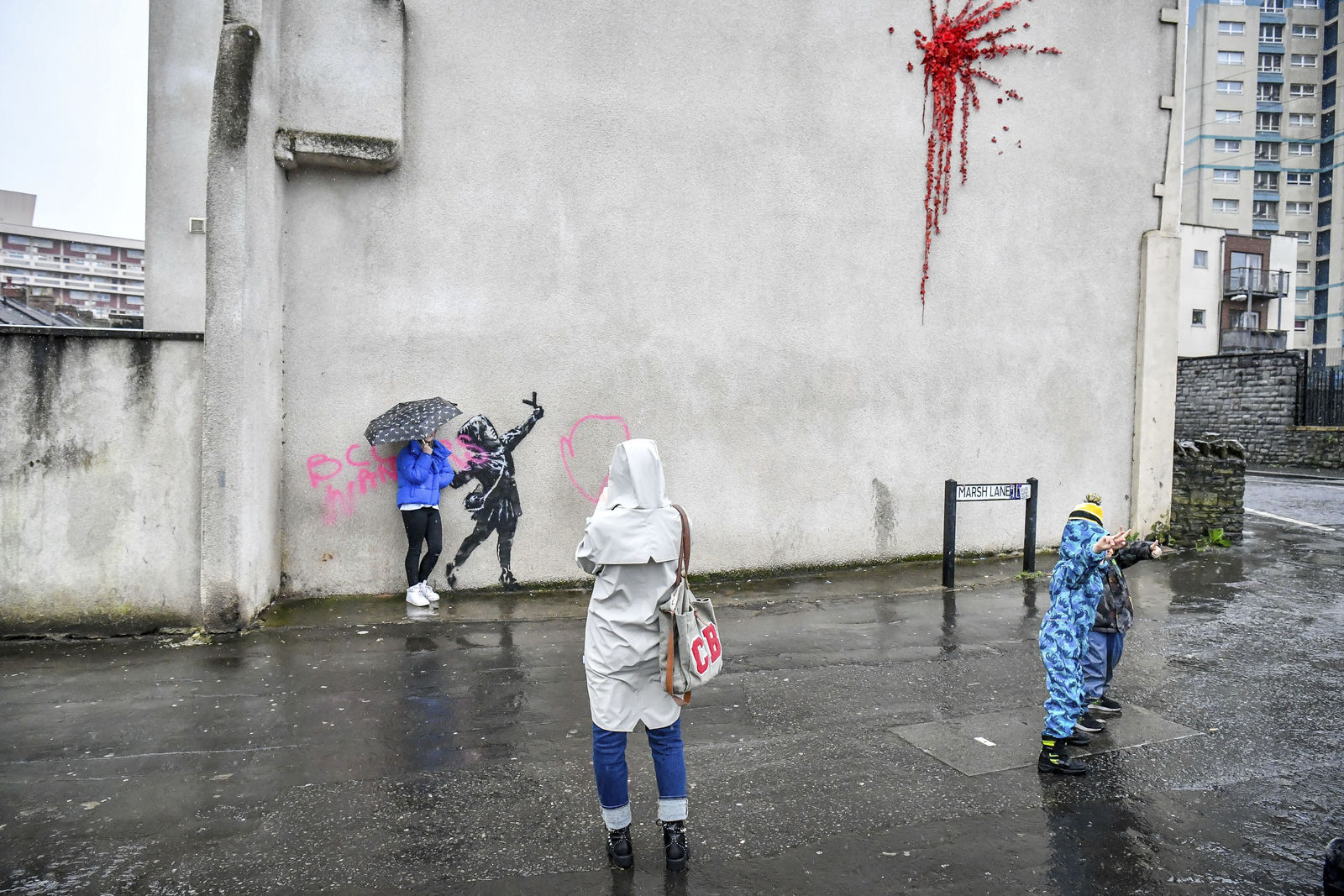 People take photos of a mural by Bansky which has been vandalised, on the side of a house on Marsh Lane, in Barton Hill, Bristol, England, Saturday, Feb. 15, 2020. The artwork was confirmed as being by artist Bansky on Valentine's day. (Ben Birchall/PA via AP)