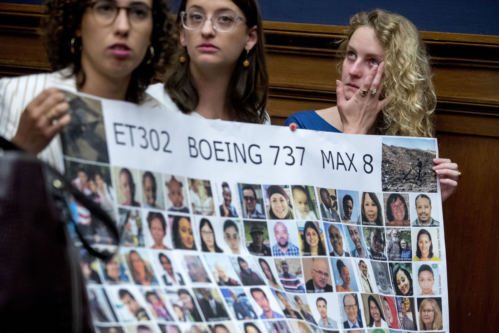 Deveney Williams, right, wipes a tear from her eye as she and Diana Sotomayor, left, and Hayley Freedman, center, all friends of Samya Rose Stumo, hold up a sign depicting those lost in Ethiopian Airlines Flight 302 during a House Committee on Transportation and Infrastructure hearing on the status of the Boeing 737 MAX on Capitol Hill in Washington, Wednesday, June 19, 2019.{ } (AP Photo/Andrew Harnik)