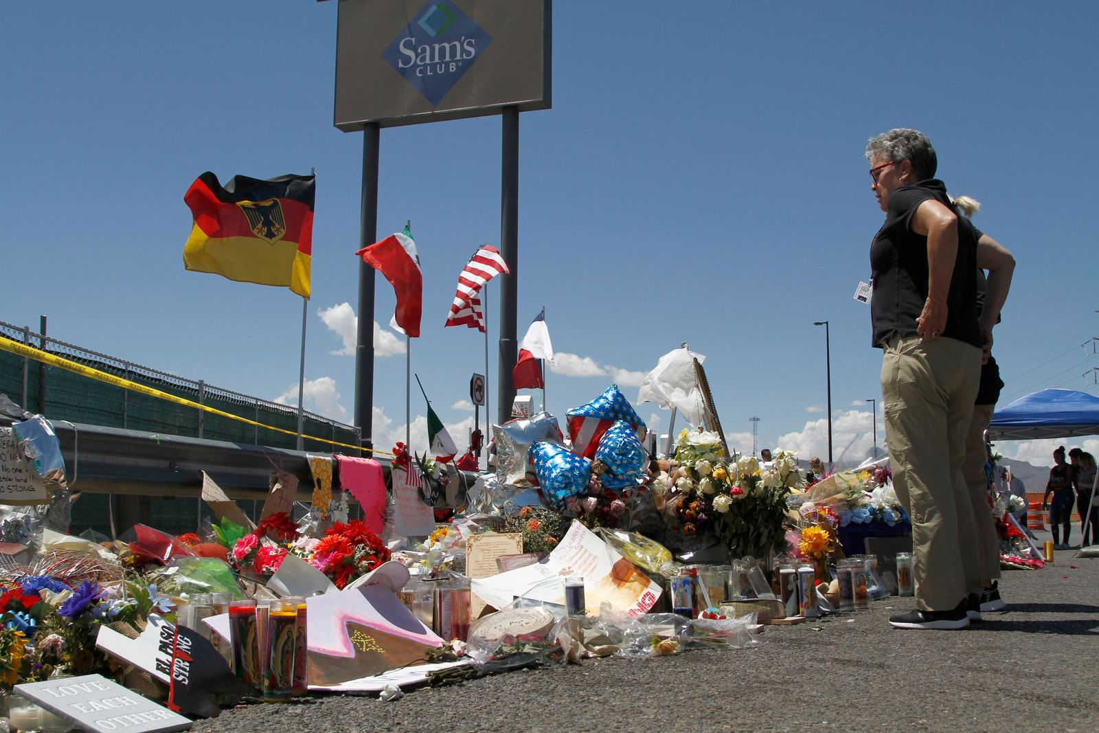 In this Aug. 12, 2019 photo, mourners visit the makeshift memorial near the Walmart in El Paso, Texas, where 22 people were killed in a mass shooting that police are investigating as a terrorist attack targeting Latinos.{ } (AP Photo/Cedar Attanasio)