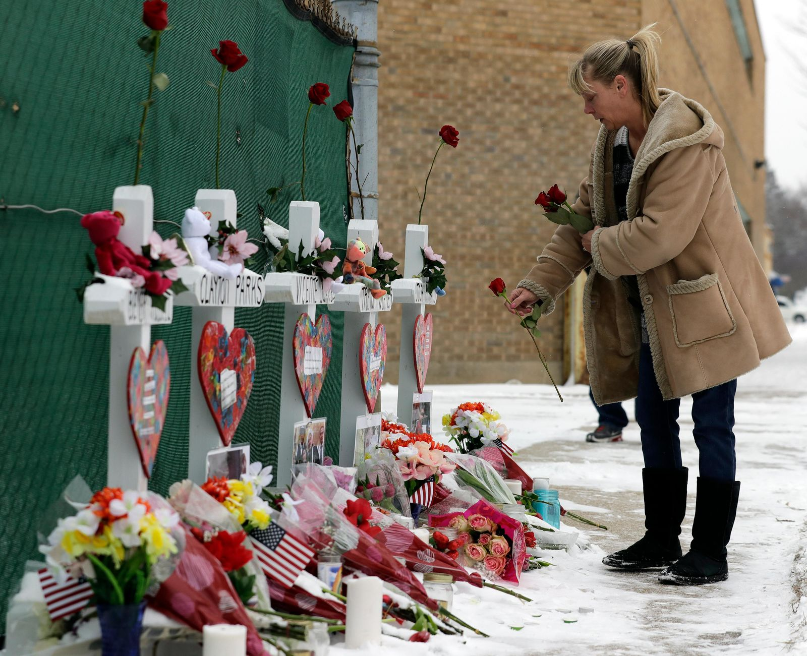 A woman places flowers at a makeshift memorial Sunday, Feb. 17, 2019, in Aurora, Ill., near Henry Pratt Co. manufacturing company where several were killed on Friday. (AP Photo/Nam Y. Huh)