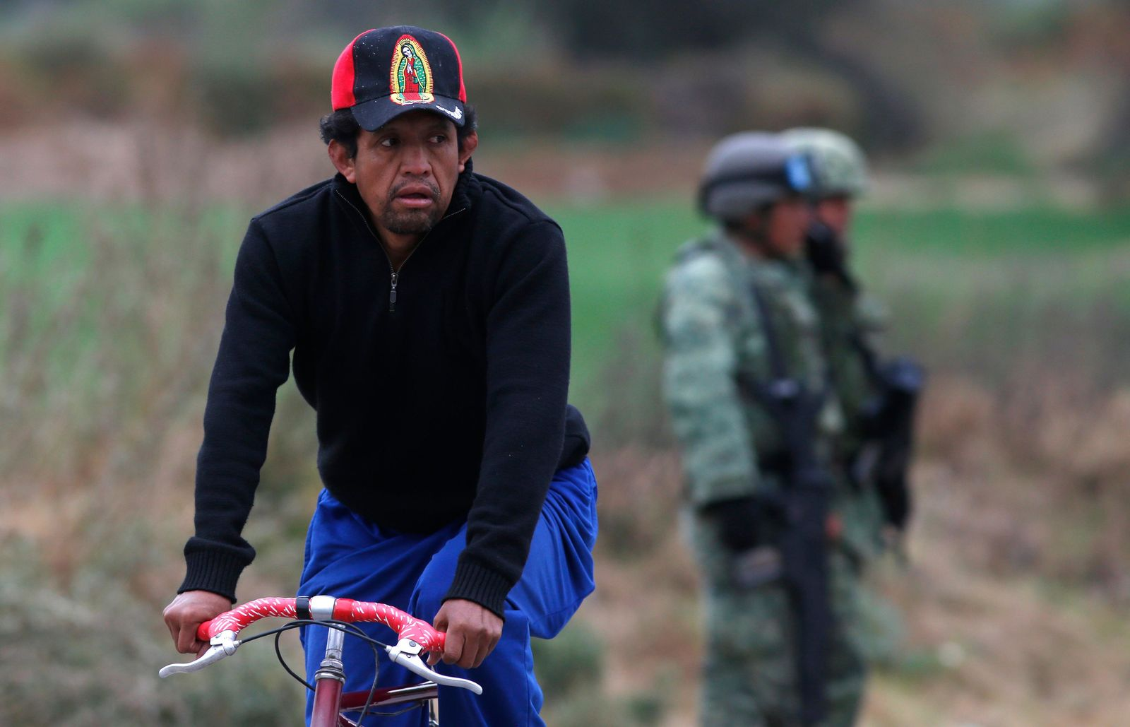 A cyclist passes soldiers who guard the site where a gas pipeline exploded two days prior, in the village of Tlahuelilpan, Mexico, Sunday Jan. 20, 2019. A massive fireball that engulfed locals scooping up fuel spilling from a pipeline ruptured by thieves in central Mexico killed dozens of people and badly burned dozens more on Jan. 18. (AP Photo/Claudio Cruz)