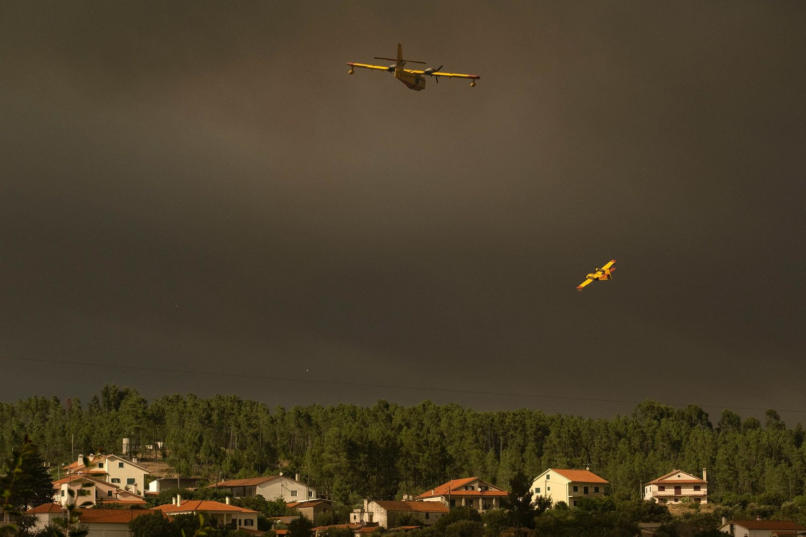 Airplanes operate over a fire at the village of Chaveira, near Macao, in central Portugal on Monday, July 22, 2019. More than 1,000 firefighters are battling a major wildfire amid scorching temperatures in Portugal, where forest blazes wreak destruction every summer. About 90% of the fire area in the Castelo Branco district, 200 kilometers (about 125 miles) northeast of the capital Lisbon, has been brought under control during cooler overnight temperatures, according to a local Civil Protection Agency commander. (AP Photo/Sergio Azenha)