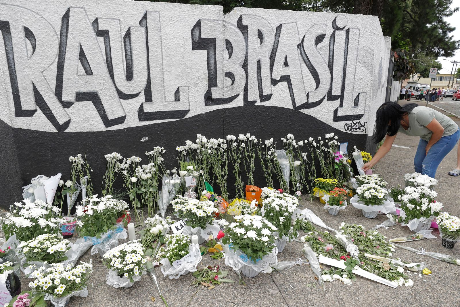 A woman leaves flowers one day after a mass, school shooting outside the Raul Brasil state school  in Suzano, Brazil, Thursday, March 14, 2019. (AP Photo/Andre Penner)