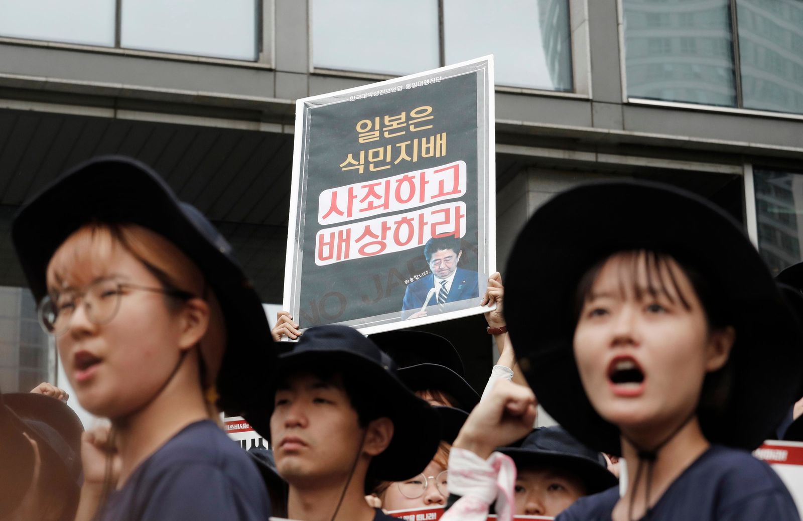 South Korean college students with a board showing an image of Japanese Prime Minister Shinzo Abe stage a rally to denounce Japan's new trade restrictions on South Korea in front of the office of Mitsubishi Corp. in Seoul, South Korea, Wednesday, Aug. 7, 2019.{ } (AP Photo/Ahn Young-joon)