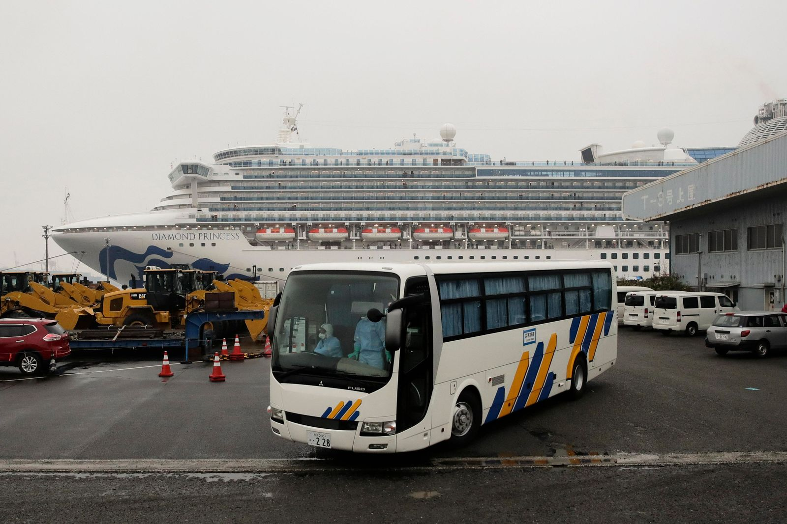 A bus leaves the quarantined Diamond Princess cruise ship at a port Sunday, Feb. 16, 2020, in Yokohama, near Tokyo. The U.S. says Americans aboard a quarantined ship will be flown back home on a chartered flight Sunday, but that they will face another two-week quarantine. (AP Photo/Jae C. Hong)