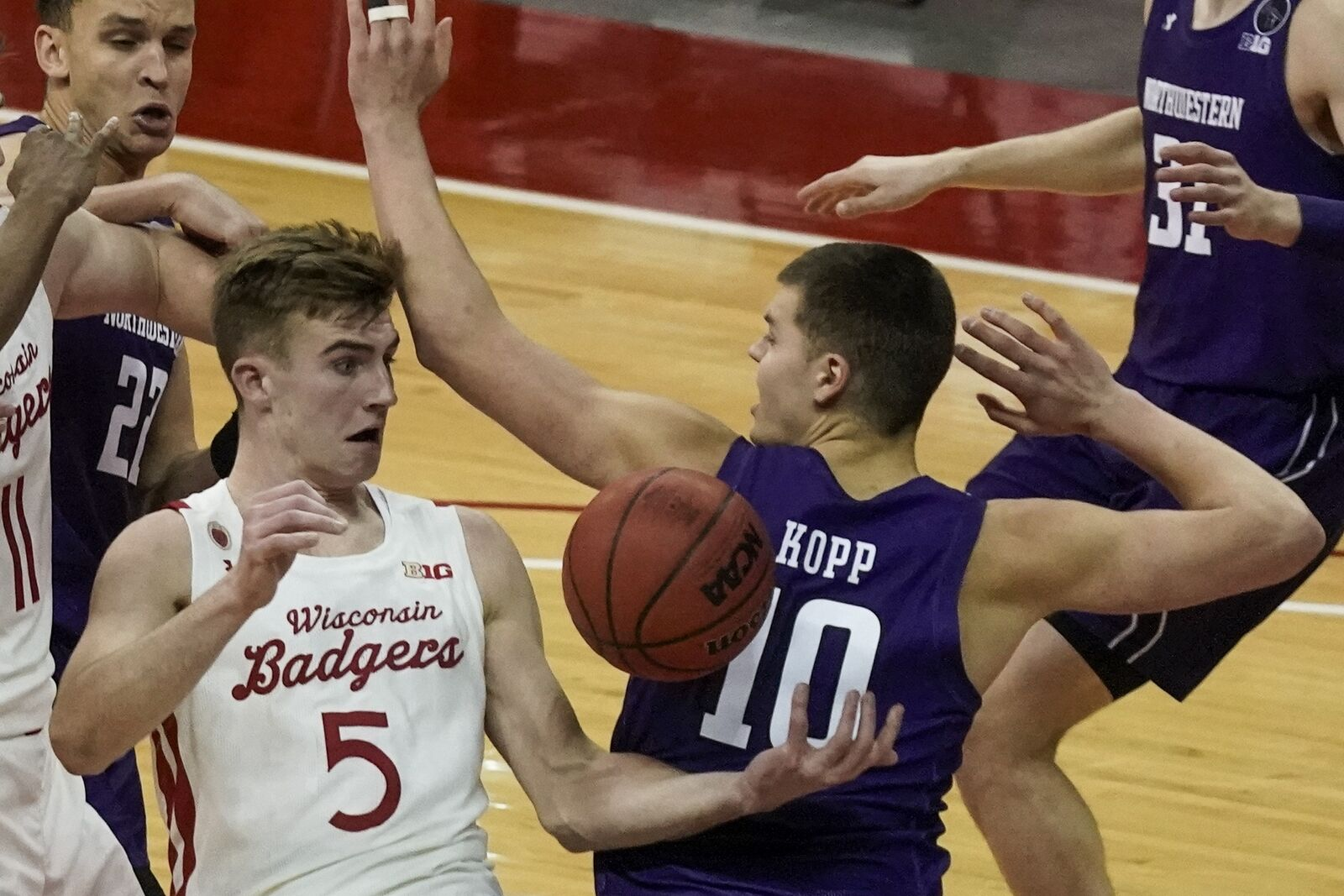 Wisconsin's Tyler Wahl and Northwestern's Miller Kopp go after a loose ball during the second half of an NCAA college basketball game Wednesday, Jan. 20, 2021, in Madison, Wis. (AP Photo/Morry Gash)
