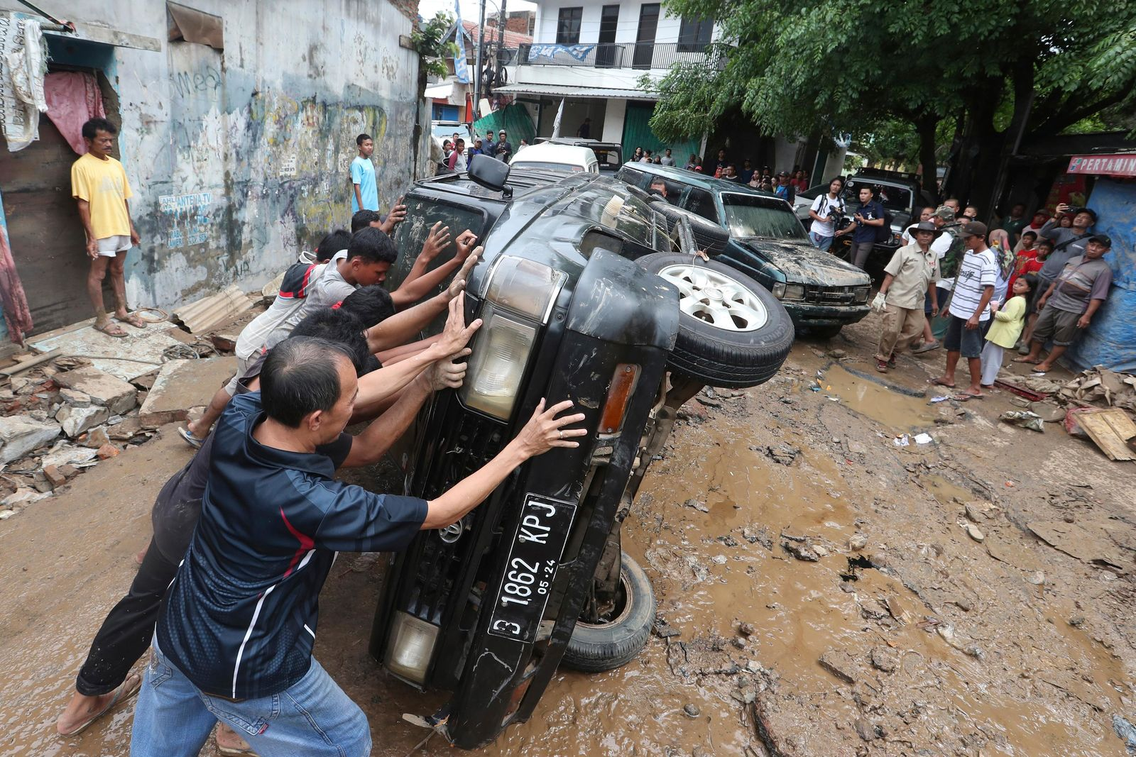 Residents move the wreckage of cars that were swept away by flood in Bekasi, West Java, Indonesia, Friday, Jan. 3, 2020.{ } (AP Photo/Achmad Ibrahim)