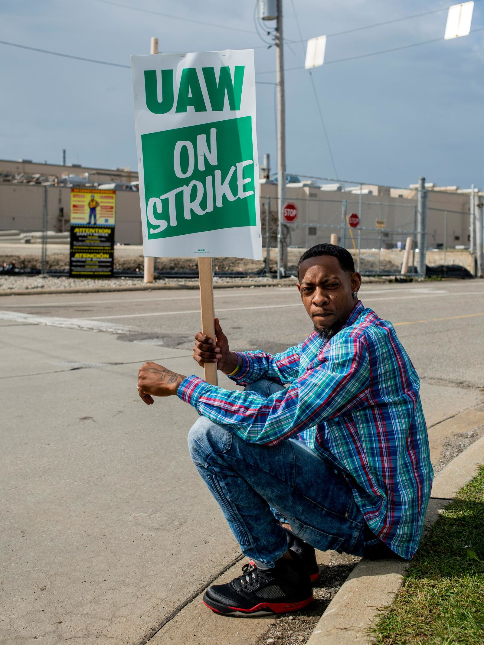 Rory Lee of Flint, Mich., sits on the curb as he protests alongside other General Motors employees outside of the Flint Assembly Plant on Sunday, Sept. 15, 2019 in Flint. GM autoworkers officially go on strike at midnight Sunday after UAW leadership voted to do so Sunday morning.{ } (Jake May/The Flint Journal via AP)