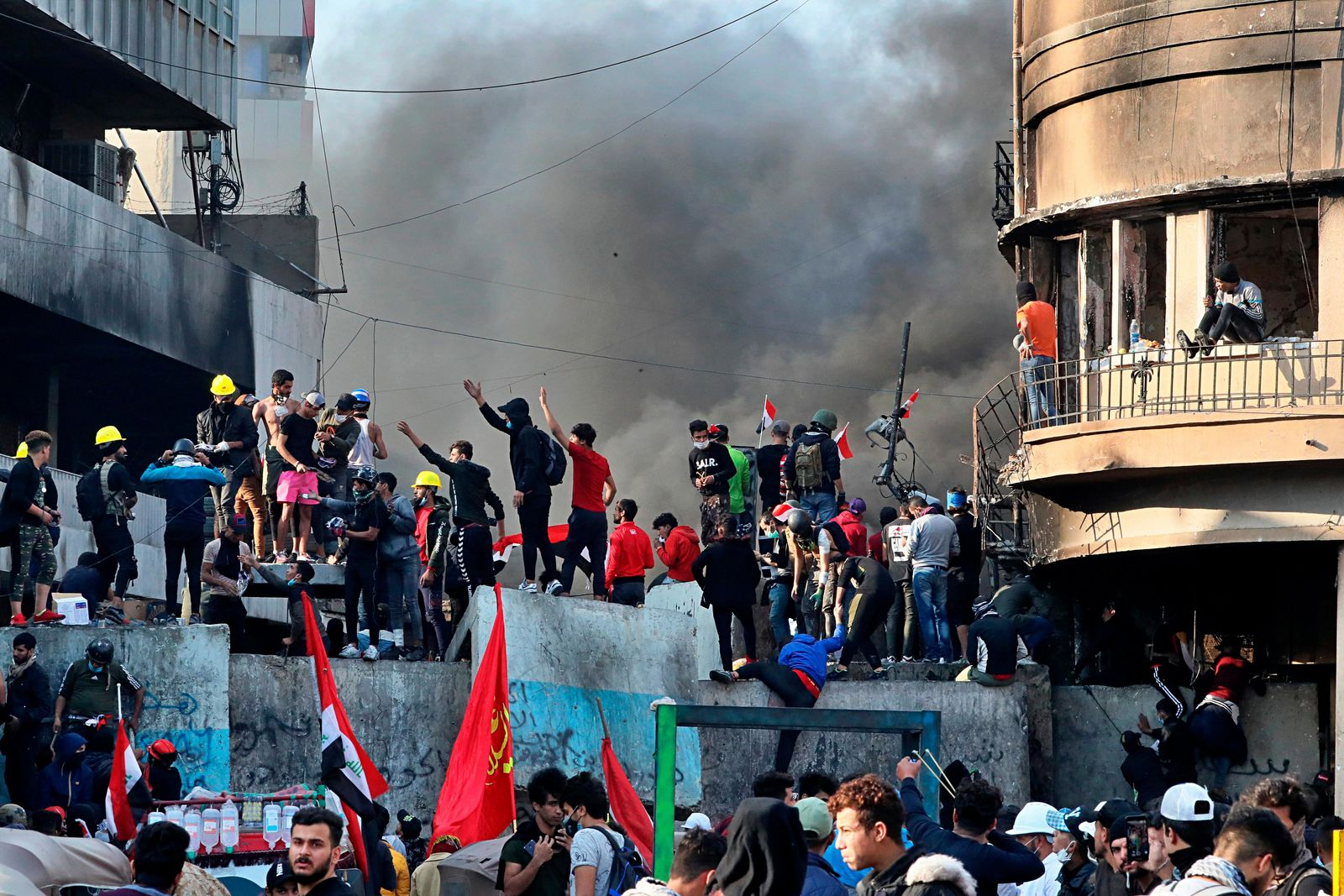 Anti-government protesters stand on a concrete wall erected by security forces to close Rasheed Street during clashes in Baghdad, Iraq, Thursday, Nov. 28, 2019. Scores of protesters have been shot dead in the last 24 hours, amid spiraling violence in Baghdad and southern Iraq, officials said. (AP Photo/Khalid Mohammed)