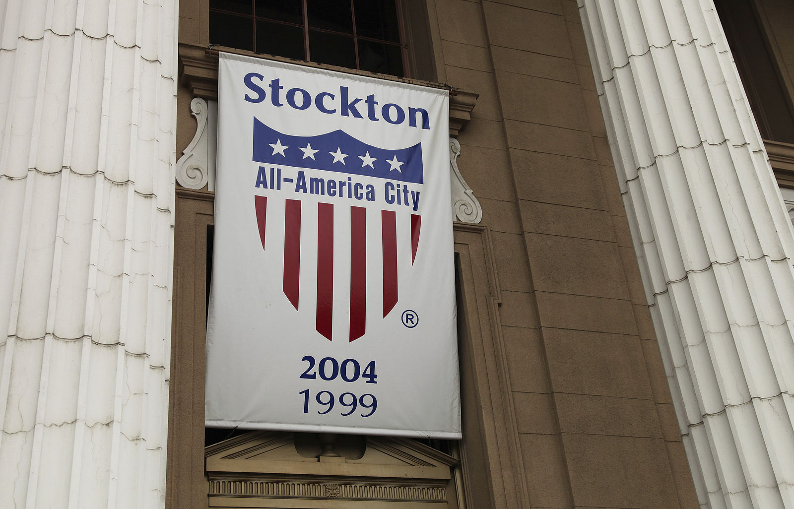 File - In this Feb. 29, 2012 file photo, a banner proclaiming Stockton as an All-America city hangs from city hall in Stockton, Calif. Stockton was once known as the foreclosure capital of the country and for one of the nation's largest municipal bankruptcies. Now, it's led by Mayor Michael Tubbs who has initiated a program to give 125 people who earn at or below the median household income of $46,033 receive a $500 debit card each month to spend any what they want. Tubbs says the program, which is privately funded, could be a solution to the city's poverty problem. (AP Photo/Ben Margot, file)