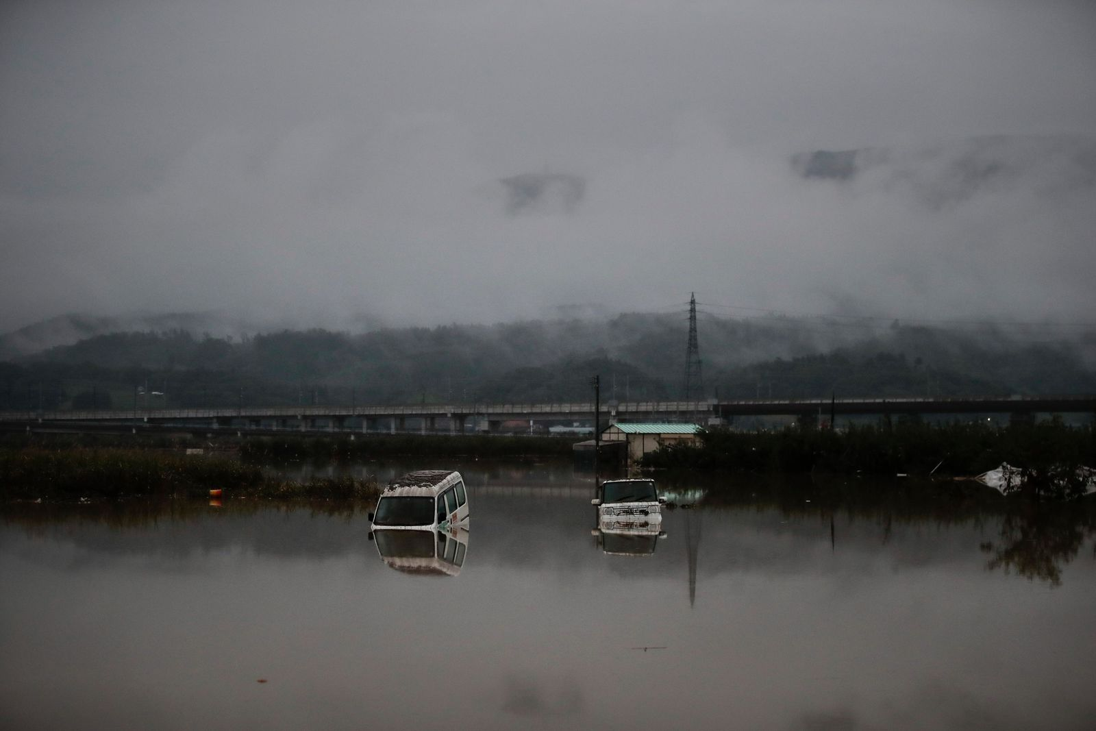 Two vehicles are submerged in floodwaters Monday, Oct. 14, 2019, in Hoyasu, Japan. . (AP Photo/Jae C. Hong)