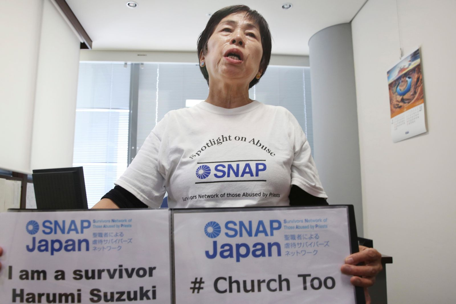 In this Nov. 25, 2019, photo, Survivors Network of Those Abused by Priests (SNAP) Japan local leader Harumi Suzuki holds signs while speaking during an interview with The Associated Press in Tokyo. Suzuki and Katsumi Takenaka are among a handful of people who have gone public as survivors of Catholic clergy sexual abuse in Japan. They held signs, when Pope Francis visited recently, standing where his motorcade passed, but in different spots and days. But they are starting to feel less alone. The Japanese bishops conference launched a nationwide investigation into sexual abuse of women and children this year, responding to the Vatican's demand for an urgent response to the global crisis. (AP Photo/Koji Sasahara)